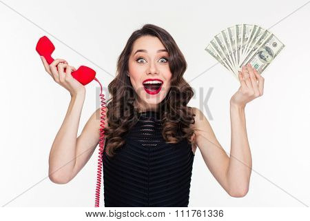 Beautiful excited happy young woman in retro style holding money and telephone receiver over white background