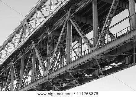 Steel truss bridge construction fragment with two levels of transportation black and white poster