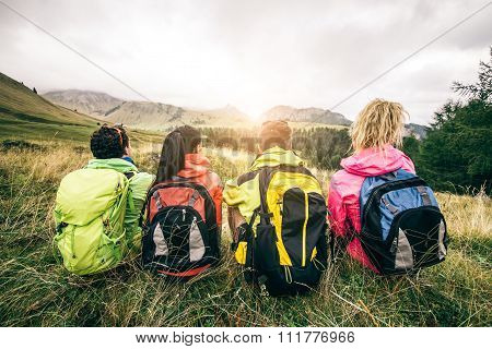 Four backpackers looking at sunset over the mountains - Hikers talking and relaxing after an excursion in the nature - Friends enjoying winter holiday poster