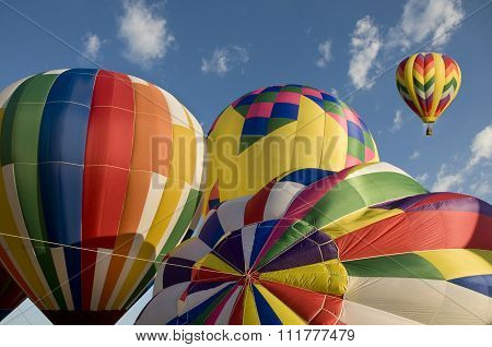 Hot-air Balloons Inflating With Another Balloon Already Aloft