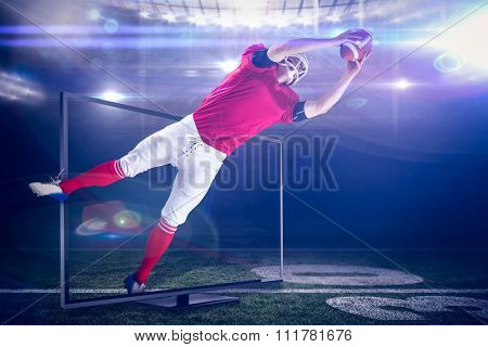 American football player catching football against american football arena
