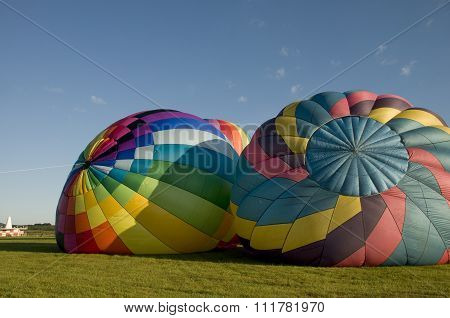 Two Hot-air Balloons Inflating On The Ground