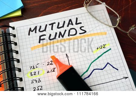 Notebook with mutual funds  sign on a table.