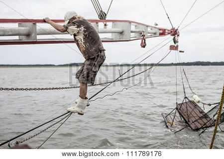 BEAUFORT, SOUTH CAROLINA-OCTOBER 16, 2015: Unidentified worker climbs the rigging on a fishing vessel off the coast of Beaufort, South Carolina