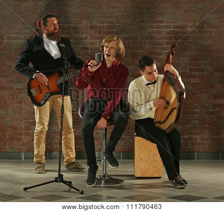 Man's musical band on brick wall background in the studio