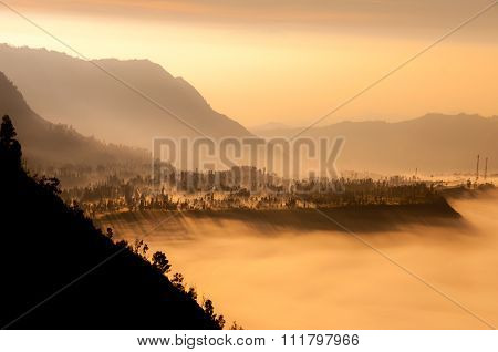 Steep black mountain silhouette in front of thick Fog Sheet