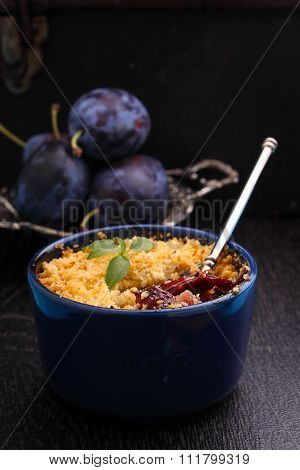 Crumble With Plums And Cinnamon On A Black Background