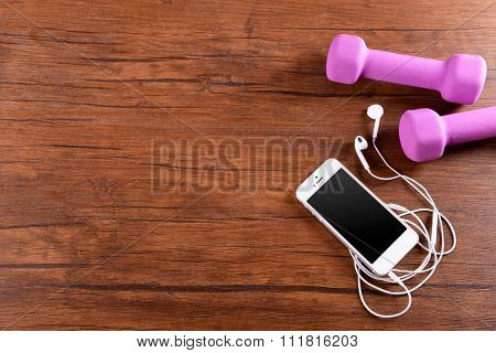 White cellphone with headphones and pink dumb bells on varnished wooden background