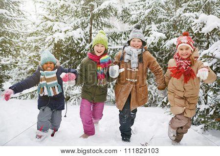 Cheerful friends in winterwear running in snow in natural environment