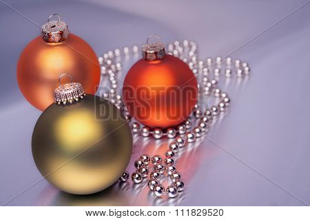 Three Christmas  balls in different colors on a violet bright background
