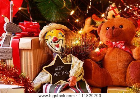 closeup of a star-shaped chalkboard with the text merry christmas and some gifts and retro toys, such as a marionette or a teddy bear, under a christmas tree ornamented with lights, balls and tinsel