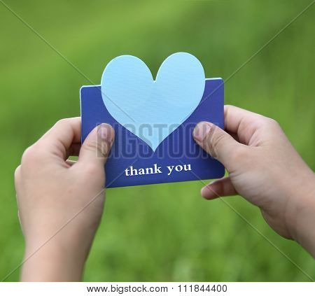 child holding a heart - shaped card