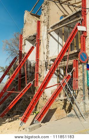Old house being restored with girders supporting its structure poster