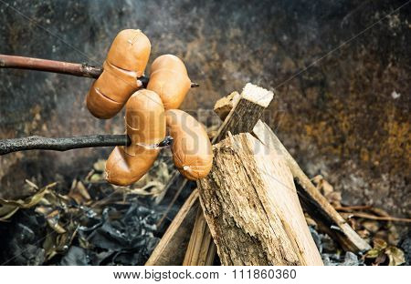 Delicious grill sausage at the campfire. Camping in nature. Outdoor activity. poster