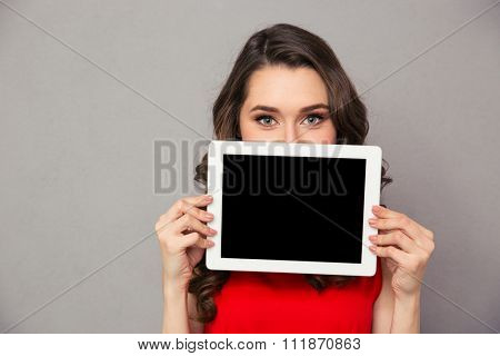 Portrait of a beautiful woman in red dress showig blank tablet computer screen over gray background