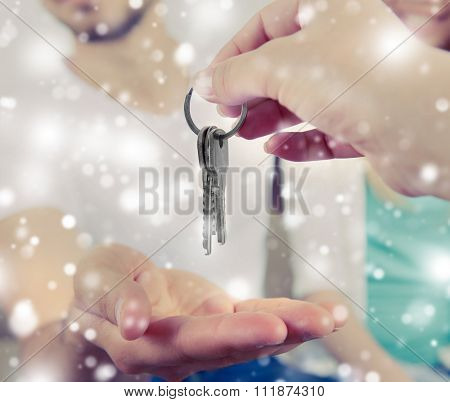 Close up of real estate agent giving keys to young couple over snow effect poster