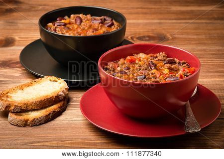 Chili con carne served in the red and black bowl on the wooden background.