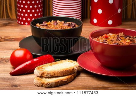 Chile con corne served in the red and black bowla on the wooden background.