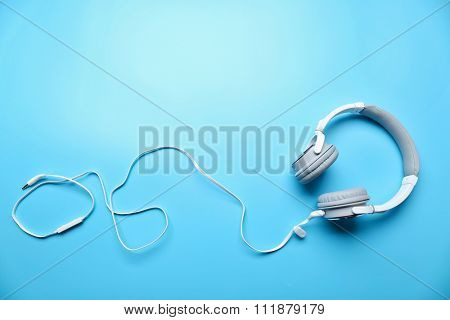 White and grey headphones on blue background