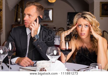 Woman at dinner date being annoyed of man talking on the phone
