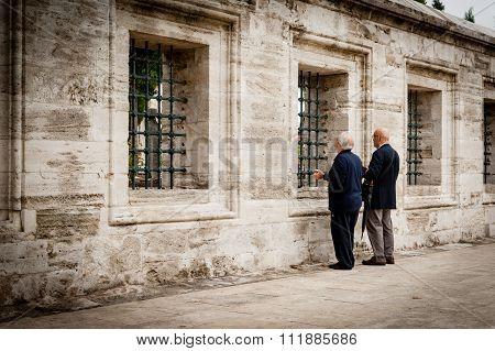 Two men praying at graveyard of a Mosque.