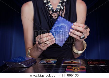 Fortune teller forecasting the future with tarot cards against large hanging curtain