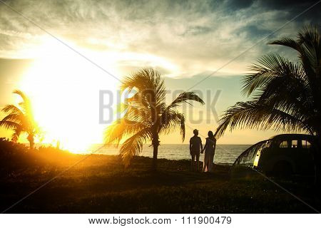 couple standing near palms on their honeymoon in sunset