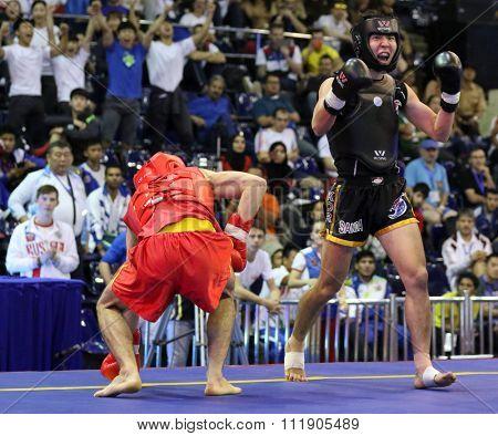 JAKARTA, INDONESIA - NOVEMBER 18, 2015: Kazbek Mamaev of Russia (red) fights Seungmo Park of South Korea (black) in the men's 65kg Sanda event at the 13th World Wushu Championship 2015.