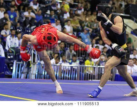 JAKARTA, INDONESIA - NOVEMBER 18, 2015: Jafar Tropraghlou of Iran (red) fights Ji Fu Xu of China (black) in the men's 65kg Sanda event at the 13th World Wushu Championship 2015.