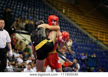 JAKARTA, INDONESIA - NOVEMBER 18, 2015: Ali Abdulkhalikov of Russia (red) fights Ayman Mohamed of Eygpt (black) in the men's 75kg Sanda semi-final event at the 13th World Wushu Championship 2015.