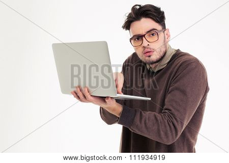 Portrait of a funny man using laptop compter and looking at camera isolated on a white background