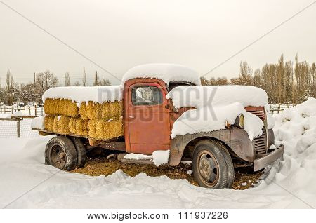 SALT LAKE CITY, UT, - DECEMBER 17: Old truck with a broken window loaded with bales of hay and covered in snow December 17, 2015 in Salt Lake City, UT.