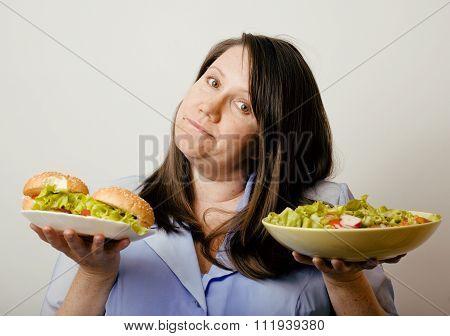 fat white woman having choice between hamburger and salad close up