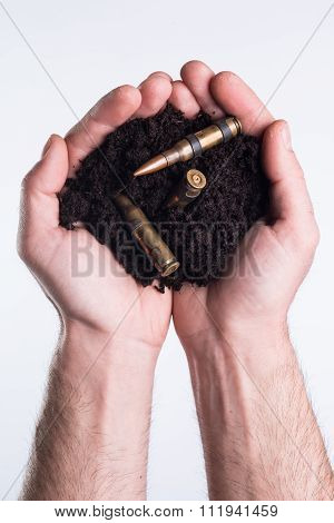 Hands Holds Topsoil With Bullets