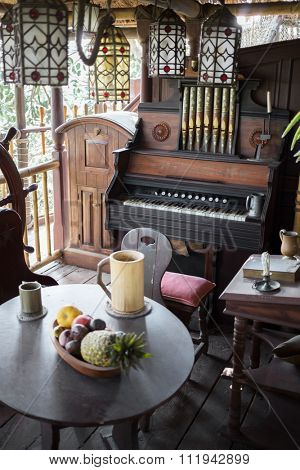 Old vintage pipe organ and table with fruits is standing outside.