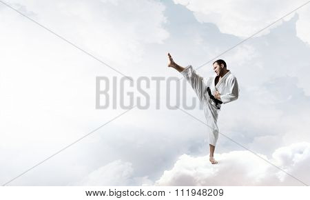 Young determined karate man on cloud high in sky