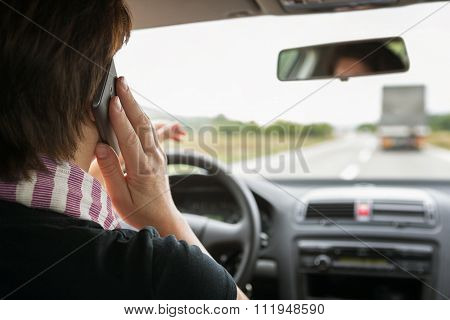 Woman using mobile phone while driving a car