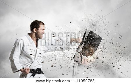 Young determined karate man breaking personal computer