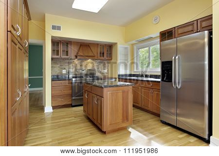 Kitchen with granite top island and yellow walls