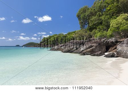 View of rocky coastline with green and turquoise water along Whitehaven Beach in the Whitsunday Islands, Queensland, Australia