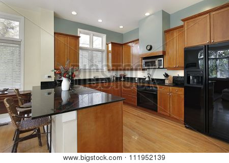 Kitchen with breakfast bar and wood cabinetry