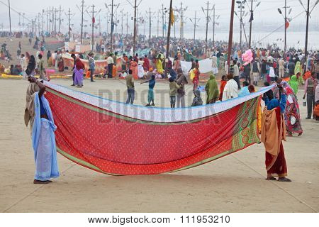 ALLAHABAD, UTTAR PRADESH, INDIA - FEBRUARY 07, 2013: Women  put their sari out to dry on wind after ritual holy bathing in the Ganges river during the festival Kumbh Mela