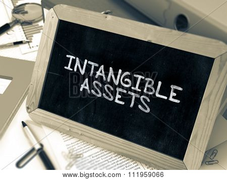 Handwritten Intangible Assets on a Chalkboard.