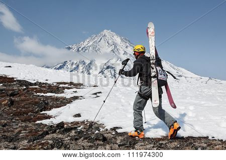Ski mountaineer climbing on mountain on background volcano