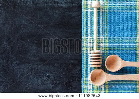 kitchen utensil and tablecloth over blackboard background