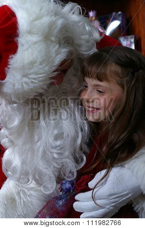 Little girl sits on Santa's knee and smiles up at Santa