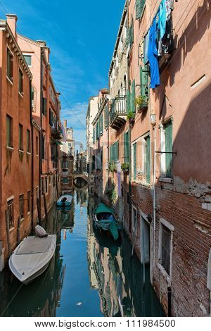 Tranquil scenic Venice, Italy, canal with colorful historic building reflected in the calm water and moored boats along the sides on a sunny day. Venice, Italy on 17 October 2015.