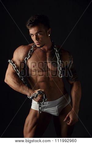 Muscular man posing with chain at camera