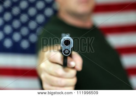 Shallow depth of field view of a hand gun being pointed directly at the camera with an American flag in the background out of focus