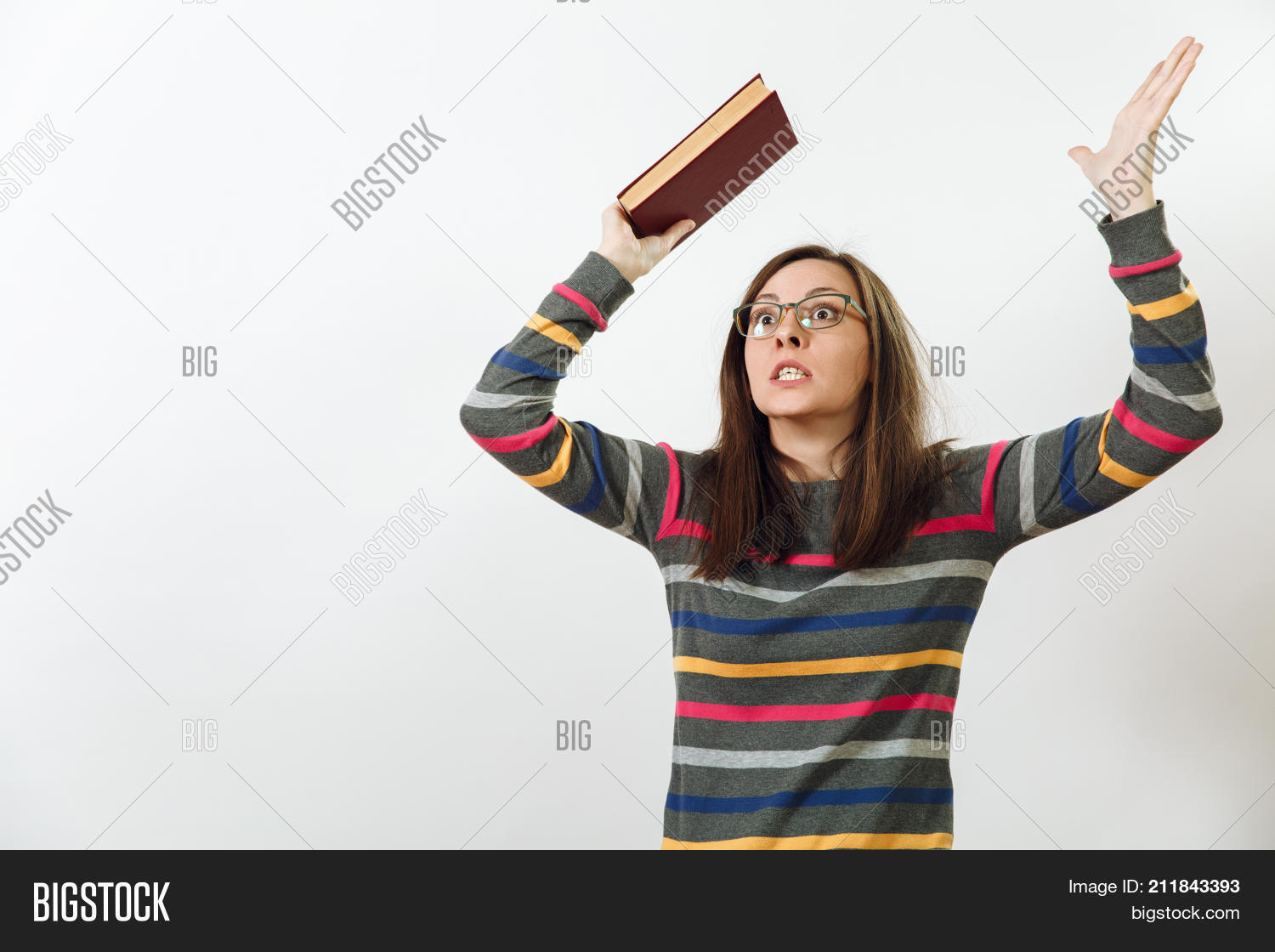4aa531293569 ... woman in glasses for sight dressed in casual dark grey longsleeve with  colorful stripes standing with book on a white background. Reading and  studying ...
